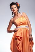 young fashion woman looking into the camera while lifting her dress with one hand. on gray background