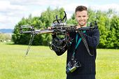 Portrait of confident male technician holding UAV octocopter in park