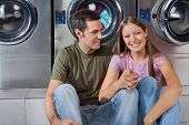Portrait of happy young woman holding man's hand while sitting at laundromat