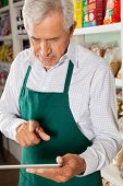 Senior male owner using digital tablet in grocery store