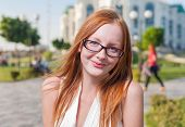 Beautiful 20s aged redhead smiling woman outdoors in glasses