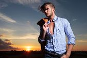 casual young man standing with a hand in his pocket while the wind blows his hair and the sun sets behind him