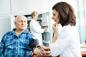 doctor measuring blood pressure of patient by phonendoscope in clinic hospital