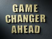 The word Game Changer Ahead in cut out paper letters on paper background