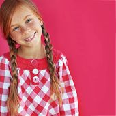 Cute redheaded child on red background