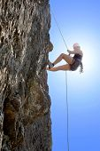 Full length of young woman climbing rock