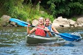 Two smiling young women kayaking down a river