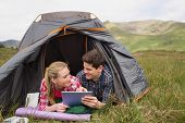 Happy couple lying in their tent and using digital tablet in the countryside