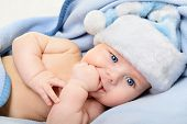 christmas cute baby boy, beautiful infant in Santa's hat and blue soft plaid with vivid positive exp