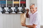 Portrait of senior man buying coffee beans from vending machine at grocery store
