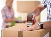 image of independent woman  - Close up of male hand packing cardboard box - JPG