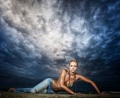 Beautiful young sexy fashion model in jeans by the sea with dramatic sky
