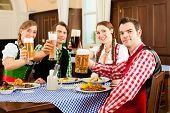 Young people in traditional Bavarian Tracht eating in restaurant or pub lunch or dinner, they toast