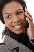 Closeup portrait of attractive afro-american businesswoman talking on mobile phone, smiling.