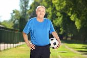 Mature man in sportswear holding a soccer ball in a park