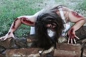 Woman zombie crawls out toward her victim