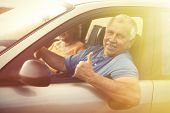 Two happy smiling elderly people in car pointing thumb