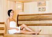 Half-naked woman relaxing in sauna. Concept of self-care, health and relaxation