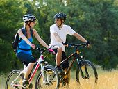 Young Happy Couple Riding Mountain Bikes Outdoor. Healthy Lifestyle Concept