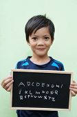 Asian boy holding a chalkboard with ABC