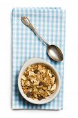 muesli in bowl and silver spoon on white background