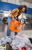 Portrait of young woman screaming while holding empty basket with clothes on floor at laundromat