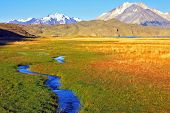 The huge valley surrounded by snow-capped mountains. Crosses the picturesque valley of the creek.  T