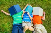 Happy Kids, Group of Young Boys Reading Books Outside Together after School