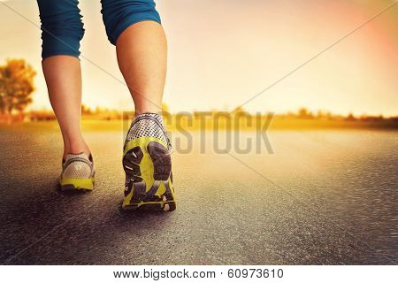 an athletic pair of legs on pavement during sunrise or sunset - healthy lifestyle concept poster