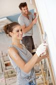 Happy young woman working on flat renovation, smiling.