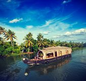 Vintage retro hipster style travel image of Kerala travel tourism background - houseboat on Kerala backwaters. Kerala, India