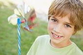 Close-up portrait of a smiling boy holding pinwheel in the park
