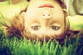 stock photo of upside  - Happy little boy standing upside down on green grass in spring park - JPG