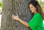 Smiling female environmentalist hugging tree trunk in park