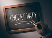 Hand writing the word uncertainty on black chalkboard