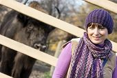 Portrait Of A Woman With The European Bison (bison Bonasus) Behind The Fence