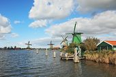Countryside - an ethnographic museum in the Netherlands. Four windmills on the banks of the channel