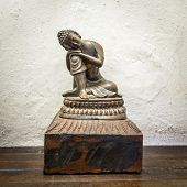 Small wooden Buddha statue, white wall background