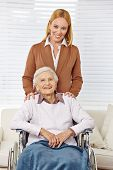 Happy family with woman and senior citizen in a wheelchair