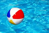 Beach ball floating in swimming pool abstract concept for summer vacations, relaxation and fun in the sunshine