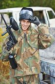 stock photo of paintball  - Happy paintball sport player man in protective camouflage uniform and mask with marker gun outdoors - JPG