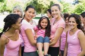 Portrait of confident multiethnic women carrying girl during breast cancer awareness at park