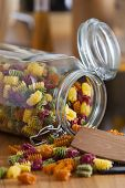 Open Storage Jar With Colorful Pasta And Cooking Spoon