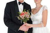 Mid section of bride and groom with flower bouquet over white background