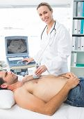 Confident female doctor using sonogram on male patient in examination room