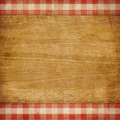 stock photo of check  - Cutting board over red grunge checked gingham picnic tablecloth background - JPG