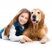 Happy cute little girl with her dog golden retriever in the studio