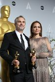 LOS ANGELES - MAR 2:: Alfonso Cuaron, Angelina Jolie  in the press room at the 86th Annual Academy Awards on March 2, 2014 in Los Angeles, California