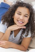 Beautiful young mixed race interracial African American girl child laying down smiling and showing o