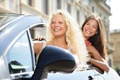 Car driver woman driving with girl friends on road trip travel vacation in convertible car in summer